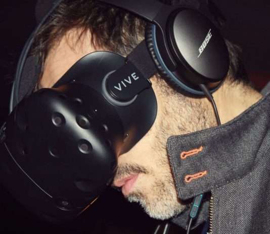 Man looking down while wearing a Vive VR headset