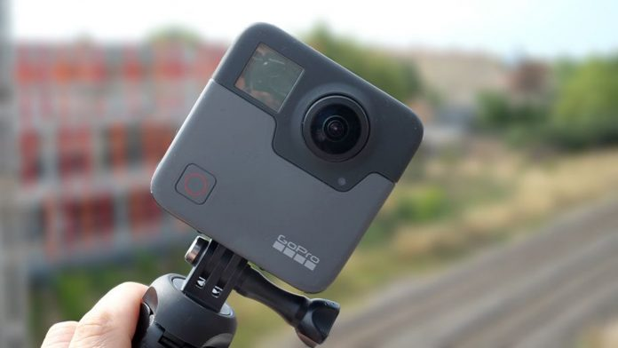A hand holding a GoPro Fusion